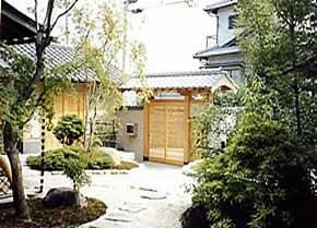 一文字瓦の数奇屋門と前庭を建物側から眺める
